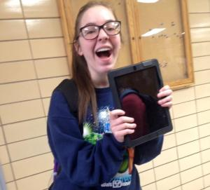 Freshman Annie Atwood hugs her iPad, which she will be able to take home with her during summer vacation. For the first time, all freshmen in the school are keeping their iPads over the break.
