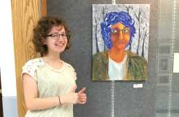 Junior Julia Kupperman poses next to a self-portrait she painted.