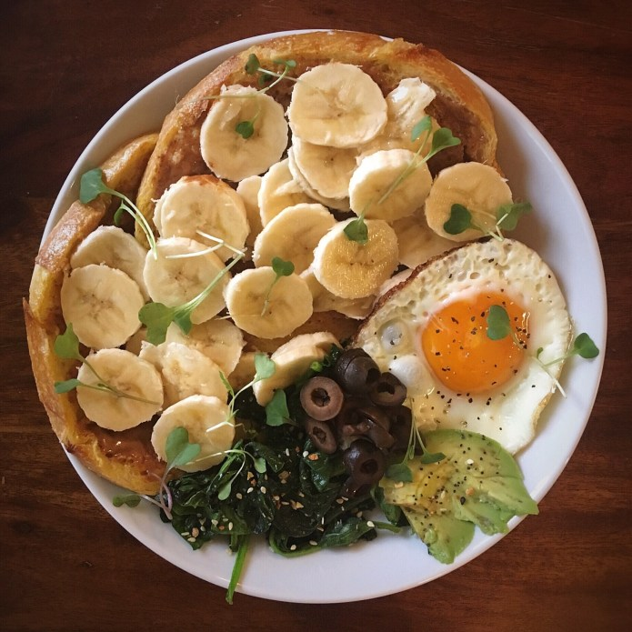 Two French Toasts with Almond Butter, Sliced Banana, Fried Egg, Spinach, Avocado, and Olives