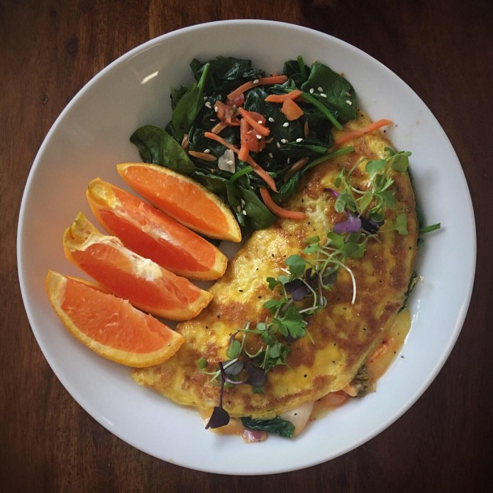 Omelette with Kimchi, Microgreens, Spinach Salad, and an Orange for Breakfast