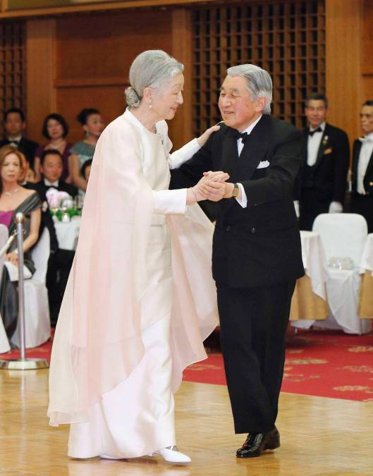Kyodo photo shows Japan's Emperor Akihito and Empress Michiko dancing at a charity dance party at a hotel in Tokyo