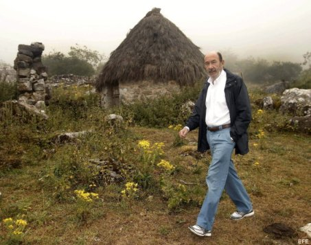 """GRA130 VILLAR DE VILDAS, 13/08/2013.- El secretario general del PSOE, Alfredo Pérez Rubalcaba, pasea ante un """"teitos"""", antiguas construcciones ganaderas con los techos de paja en Villar de Vildas, una pequeña localidad de montaña del suroccidente de Asturias en la que se ha reunido con ganaderos y ha visitado el Parque Natural de Somiedo Rubalcaba, ha acusado hoy al PP de tener """"abandonadas"""" las políticas para el medio rural a corto y medio plazo y de poner en peligro los ayuntamientos de este ámbito con una reforma de la administración local que puede dejar sin servicios sociales a los núcleos más pequeños.     EFE/Alberto Morante"""
