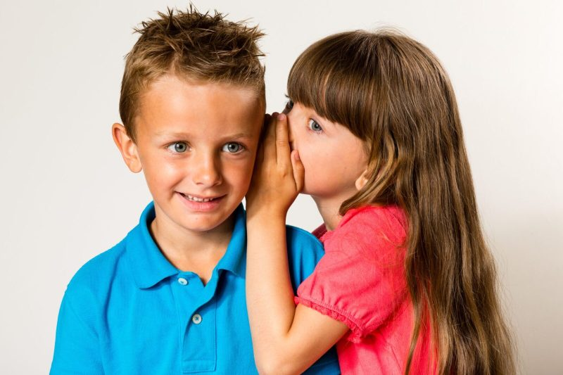 A young girl telling a secret to a young boy. Isolated on white background.