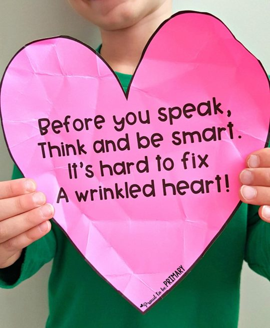 teaching empathy skills: child holding up wrinkled heart for empathy activity and poem