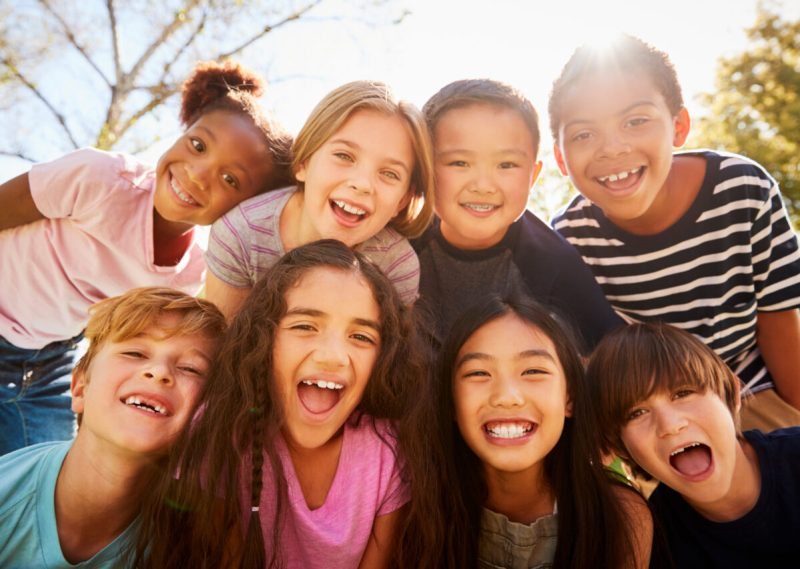 group of kids together smiling outside