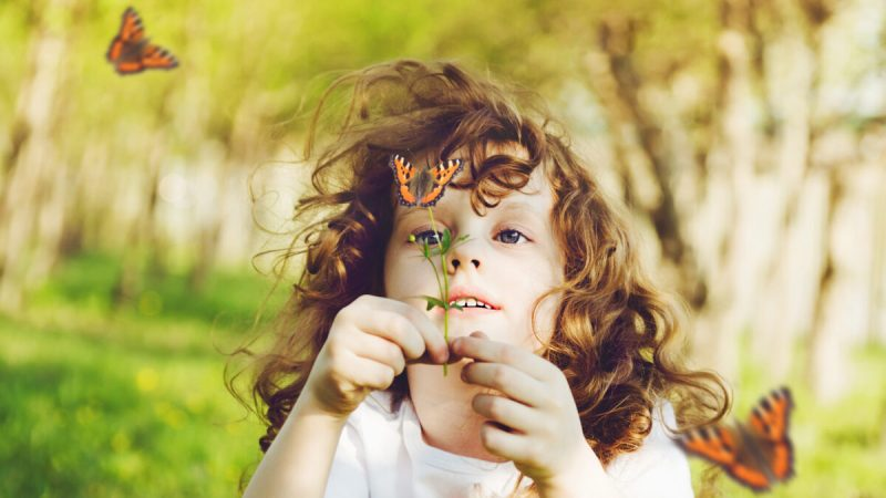 child holding flower up for butterflies flying around