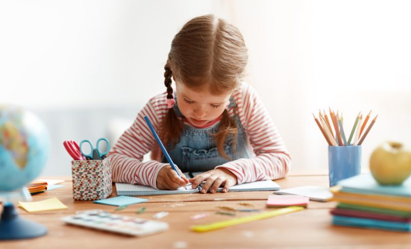 girl writing independently at a desk
