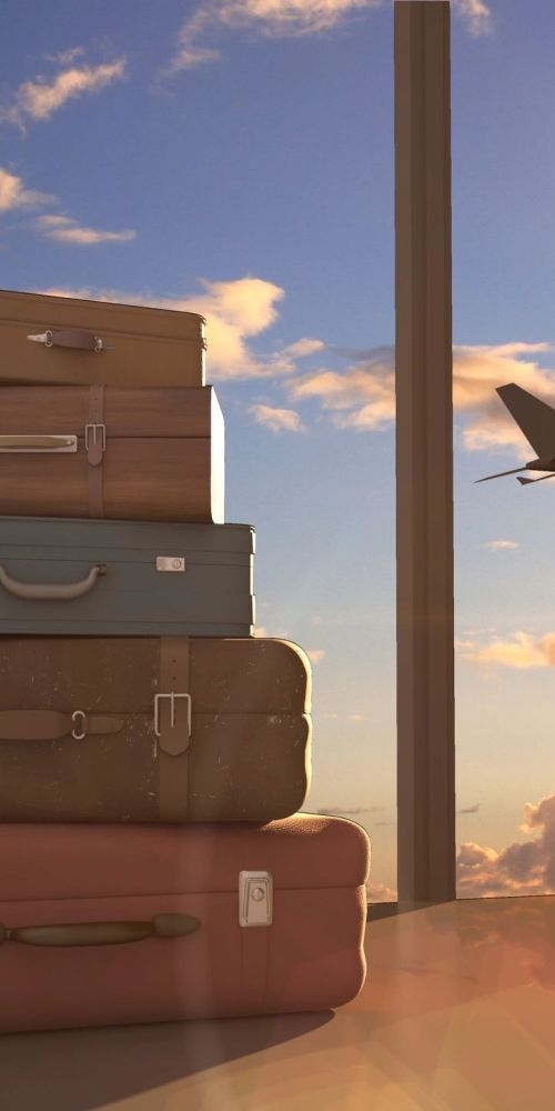 Stack of colorful suitcases in an airport with a plan ascending outside the window