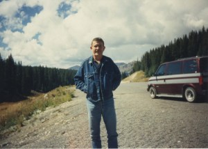 The author's father on a road trip, with pine trees and mountains in the background