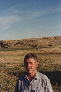 The author's father with a big sky and rolling hills behind him