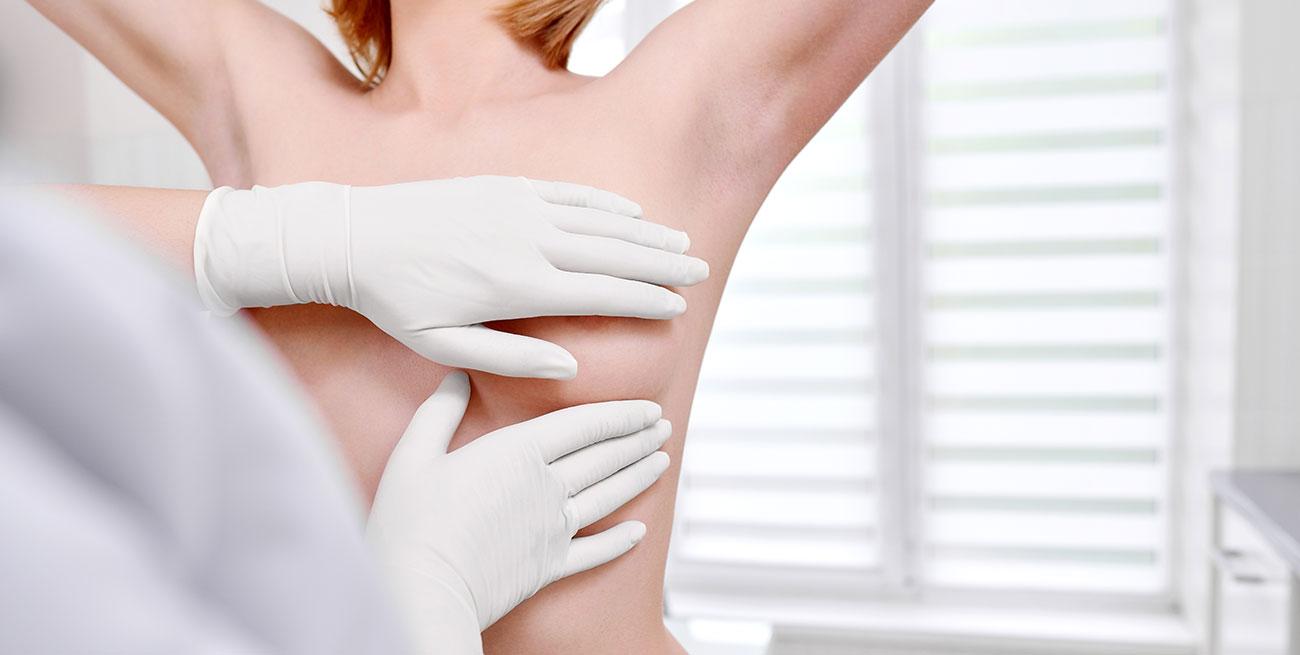 Médico faz exame clínico de mamas de mulher