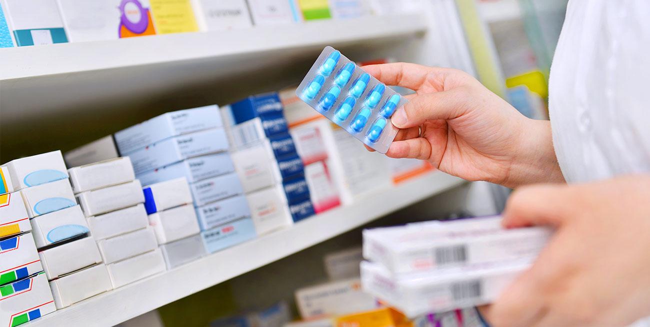 Farmacêutica segura cartela de medicamentos azuis na frente de prateleira de remédios