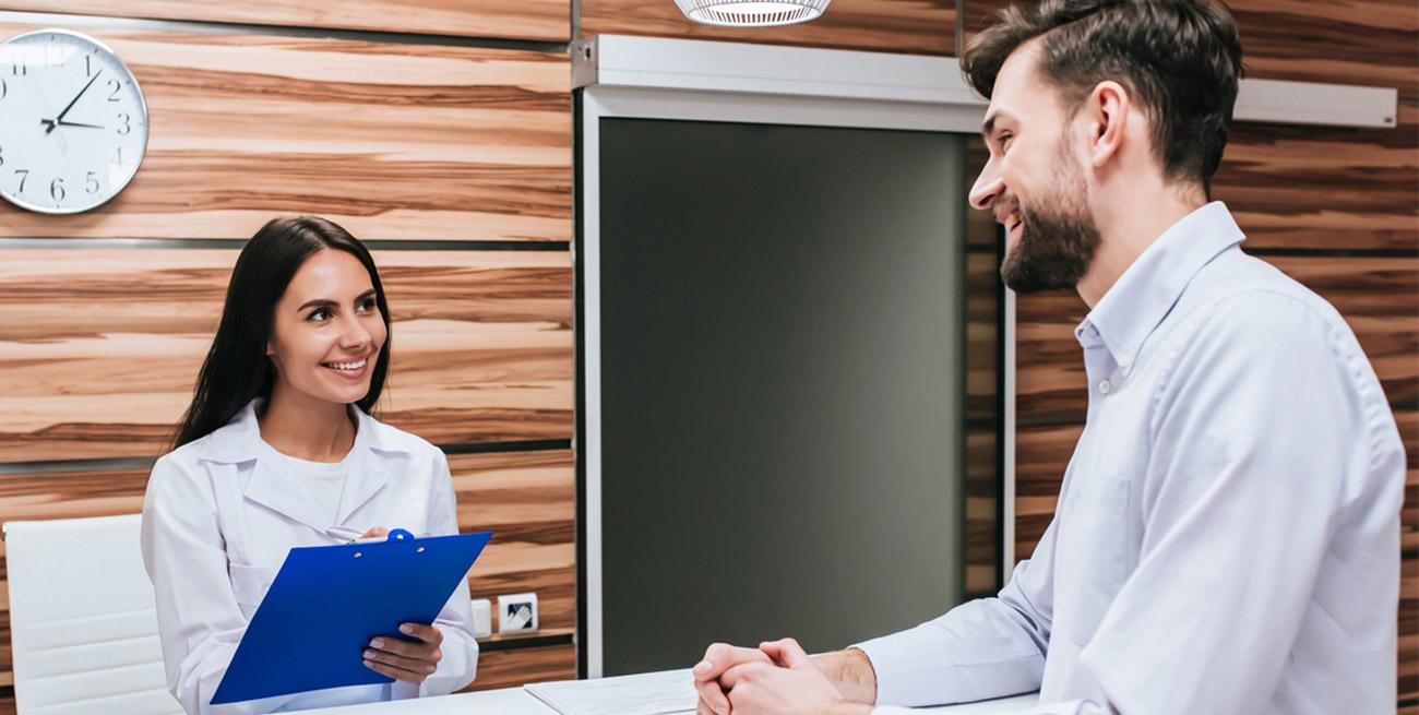 Recepcionista atendendo paciente em consultório