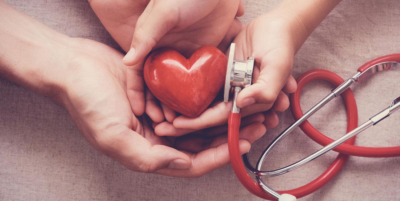 Mão segurando um coração ao lado de um estetoscópio