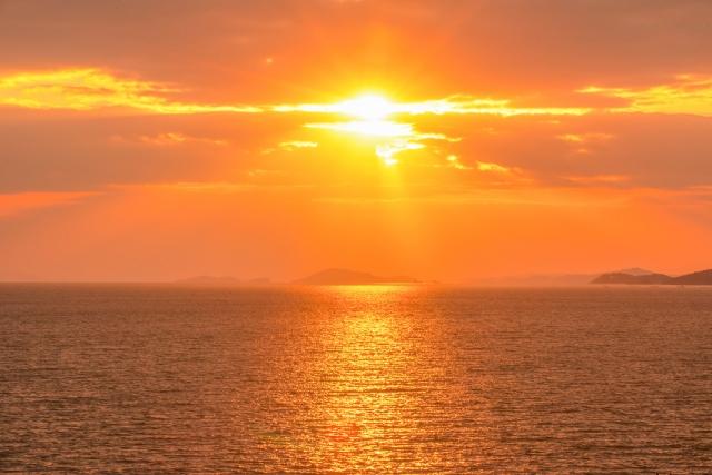 秋空に金色に輝く日本一の西伊豆の夕日のイメージ