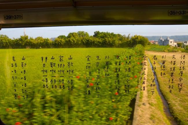 山歌列車の窓から外を見ると、「山歌一條路」の歌詞と田んぼの景色が重なる。(画像提供:Akibo works 明道スタジオ 写真:施翔允)