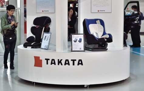 (FILES) - A file picture taken on November 11, 2014 shows visitors look at displays of Japanese auto parts maker Takata Corp at a car showroom in Tokyo on November 11, 2014. Embattled Japanese auto parts maker Takata has published an open letter in major US and German media, vowing to step up its safety record after an airbag crisis hammered the company's reputation. AFP PHOTO / KAZUHIRO NOGI / FILES
