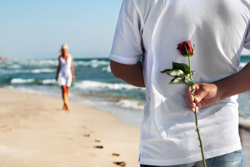happily-ever-after-man-holding-red-rose-woman-walking-beach
