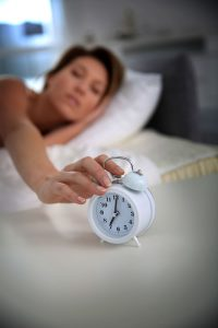 snooze-woman-reaching-clock