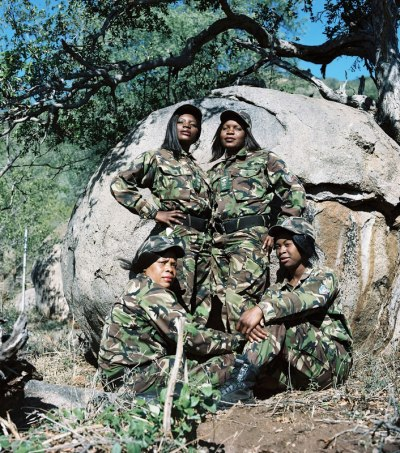 Black Mambas Women Anti-poaching Unit - group-of-women-sitting-and-standing-in-front-of-large-boulder