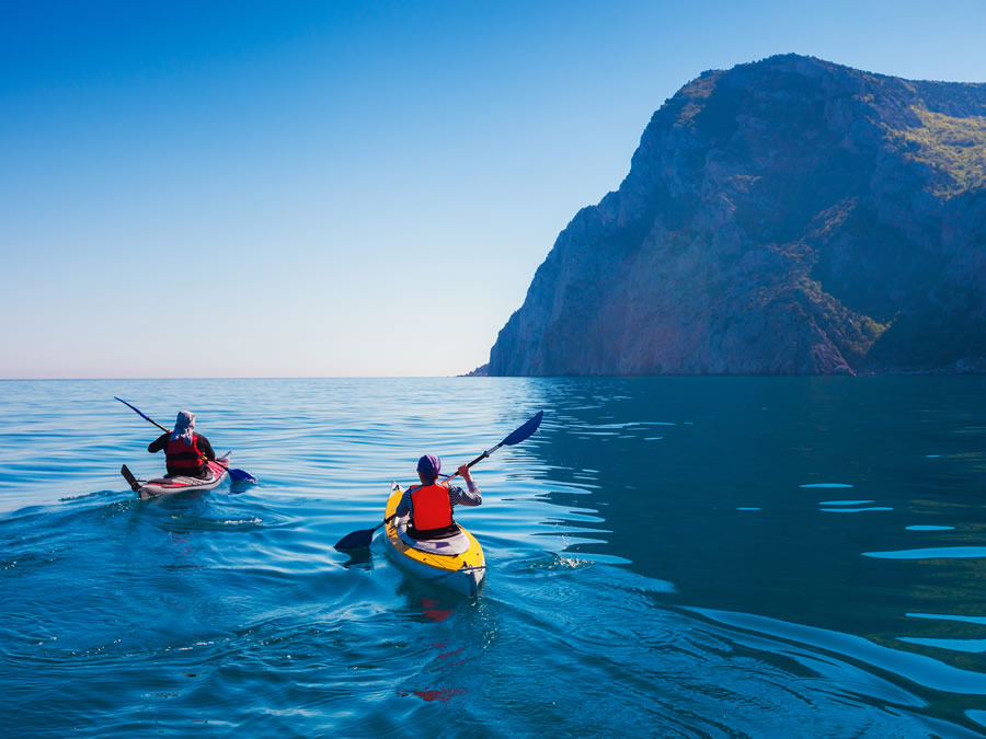 moving-kayaks-couple-kanoeing-in-the-sea-near-the-island-with-mountains-people-kayaking-in-the-ocean