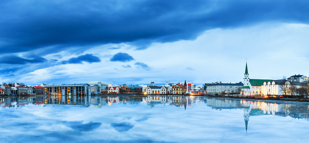 panorama of the skyline cityscape of Reykjavik, reflected in lake Tjornin at the blue hour in winter