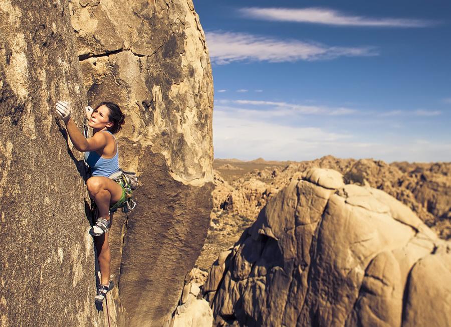 Grit - woman-climbing-vertical-cliff