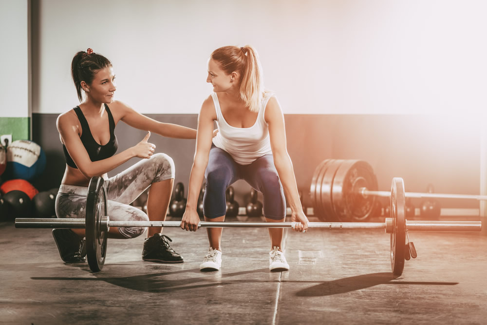 female personal trainer with woman lifting weights