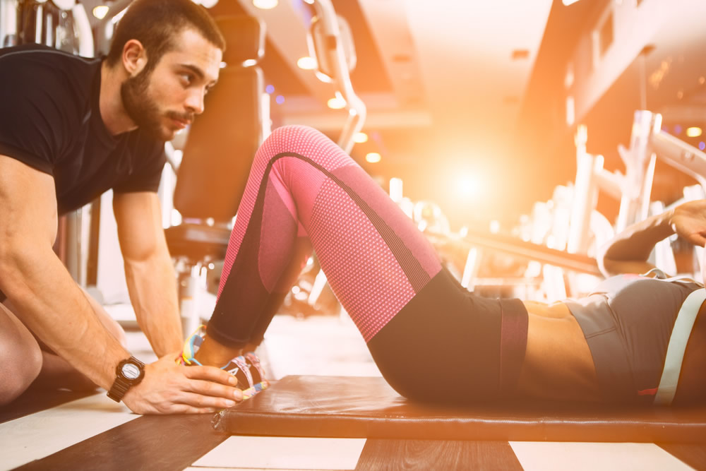 male personal trainer with woman on floor in gym