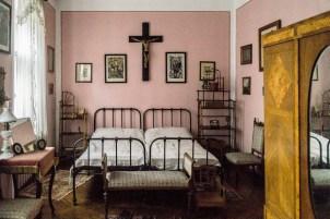 łóżko z obrazami i dużym krzyżem nad nim