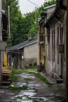 wąska brukowana uliczka ze starymi zniszczonymi domami