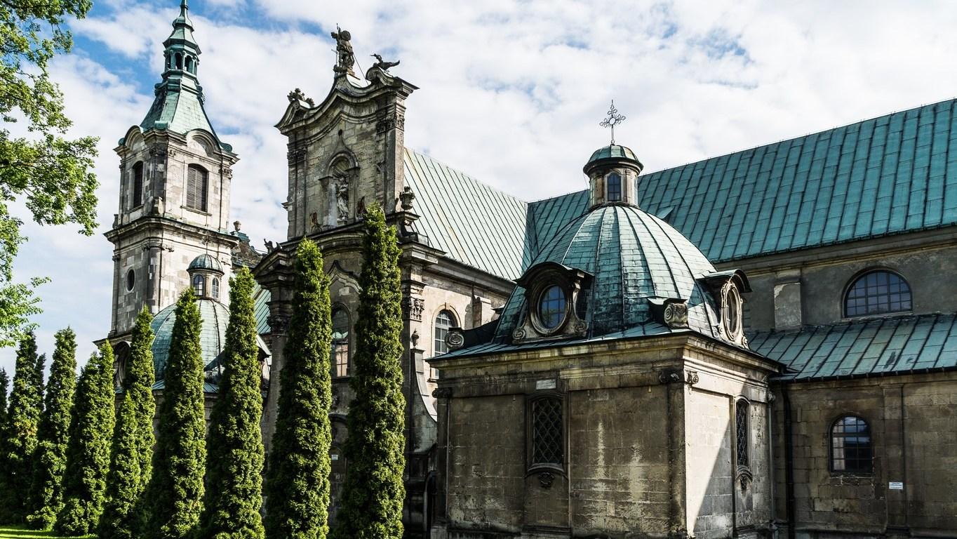 kamienne budynki sakralne częściowo przysłonięte zielenią