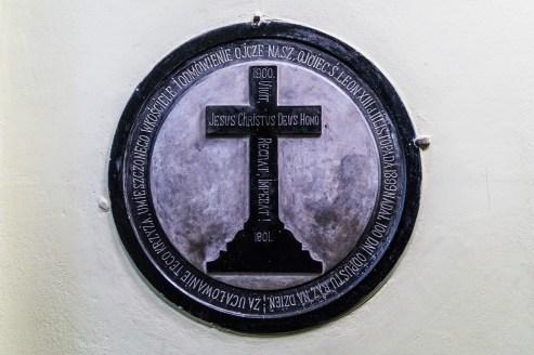 krzyż na ścianie kościoła otoczony inskrypcjami