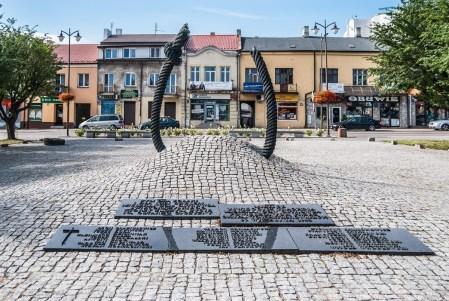 pomnik w kształcie sznura na tle kamienic