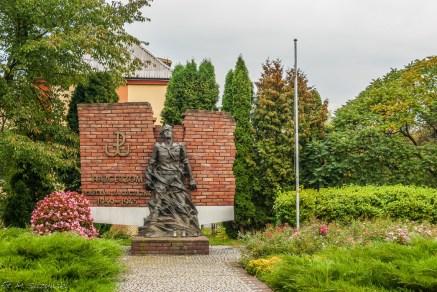 pomnik człowiek na tle kamiennego muru z symbolem Polski Walczącej
