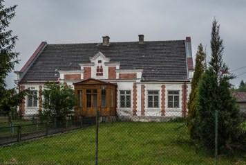 biało czerwony budynek z drewnianym gankiem