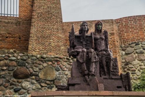 pomnik mężczyzny i kobiety na tle murów miejskich