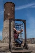 podsumowanie maja - człowiek w klatce na tle wieży zamkowej