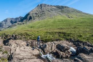 mężczyzna idacy po skałach w tle góra