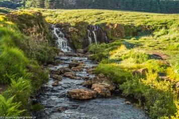wodospady na małej rzece wsród zielonych łąk