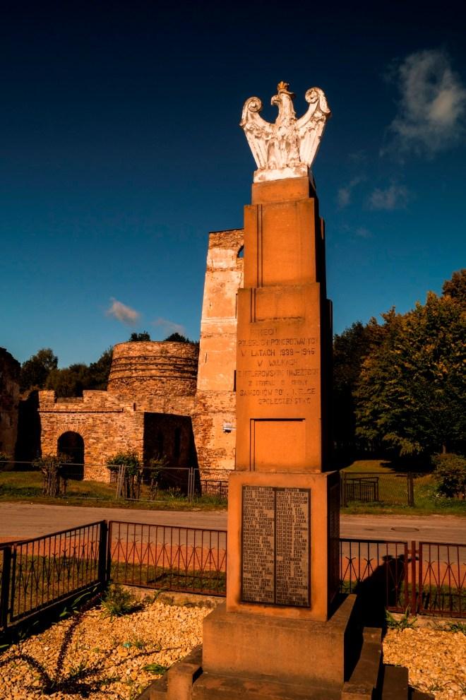 Samsonów - Pomnik Pomordowanych, w tle ruiny huty