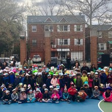 First grade students pose with their hats in the school yard