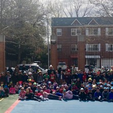 Third grade students pose with their hats in the school yard