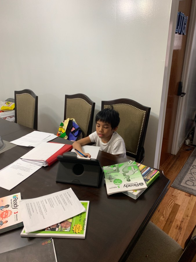 A student working at a kitchen table who appears to be very tired