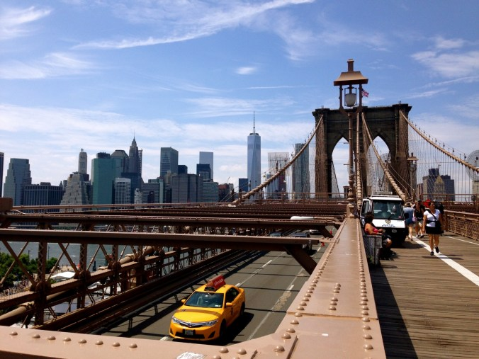 Brooklyn bridge with a view of the Manhattan skyline in the background