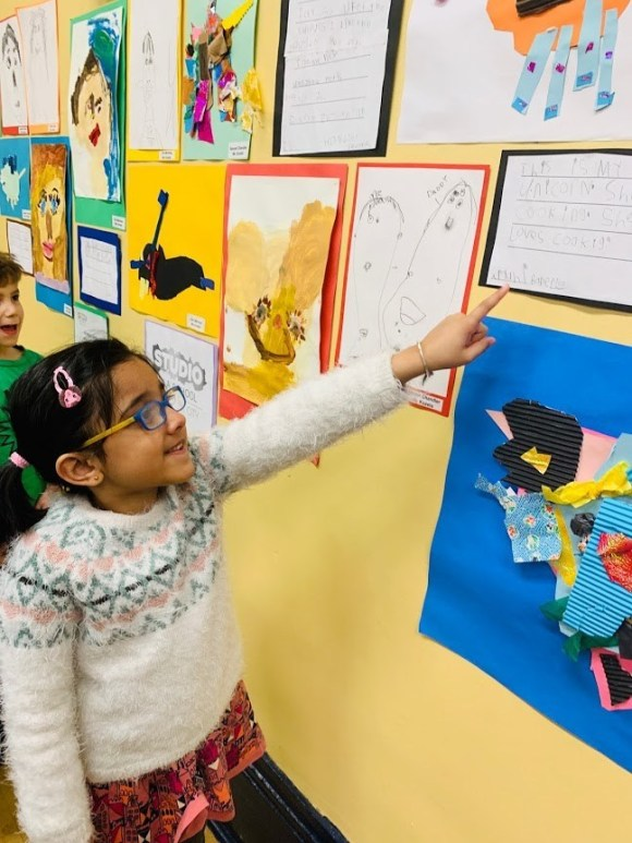 student pointing to her work on the ps8 wall