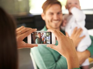 Shot of a young woman taking a photo of her husband and child with a cellphone