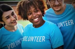 three people smiling wearing blue volunteer shirts