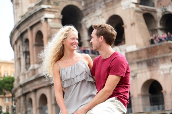 Travel couple in Rome by Coliseum in love. Tourists dating laughing having fun. Two happy young tour