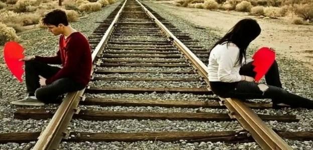 casal sentado no trilho com coração partido